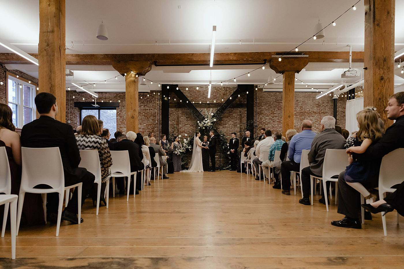 Bride and groom hold hands during ceremony at Irving Steet Studio Wedding