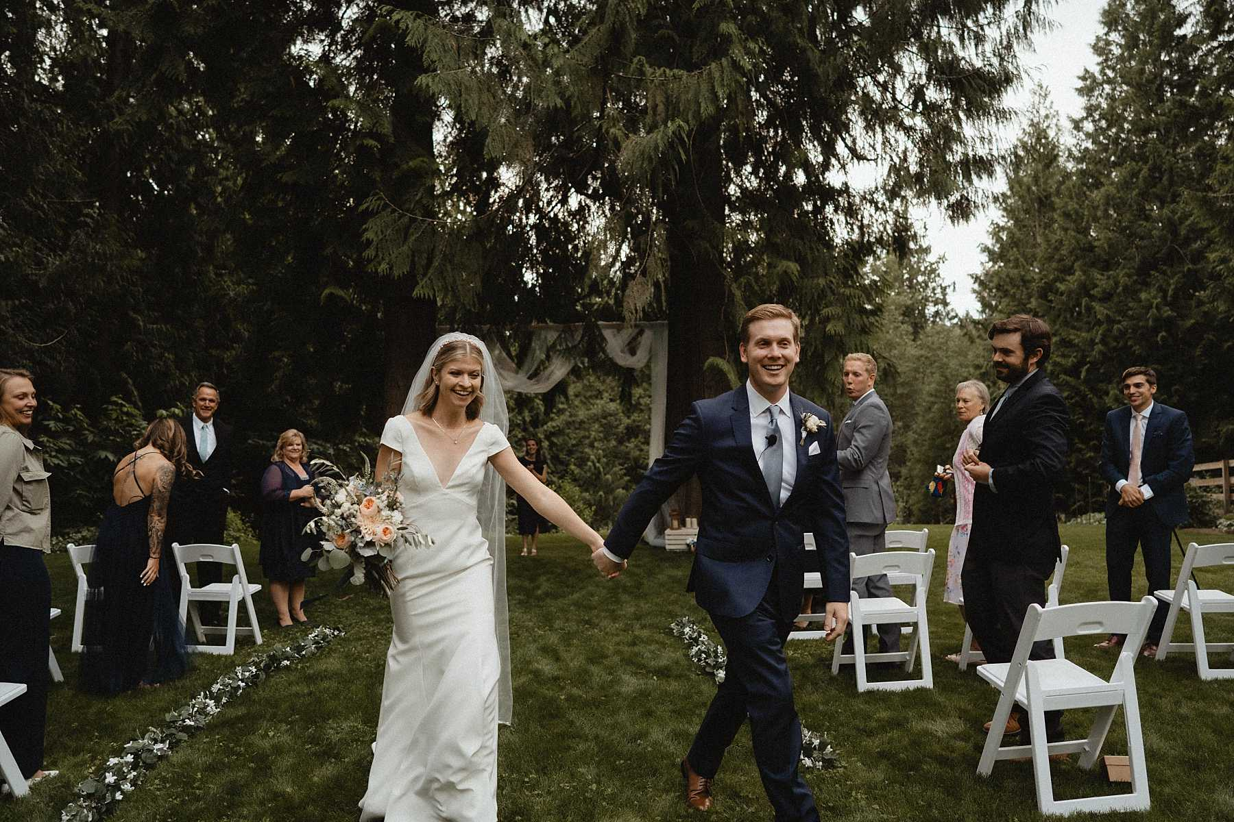 Bride and groom walk down the aisle during seattle backyard wedding