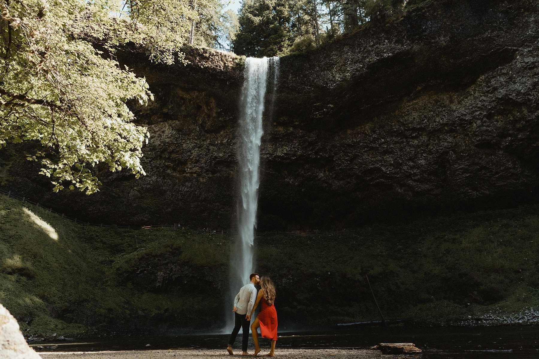 overlooking their first waterfall during the silver falls state park engagement