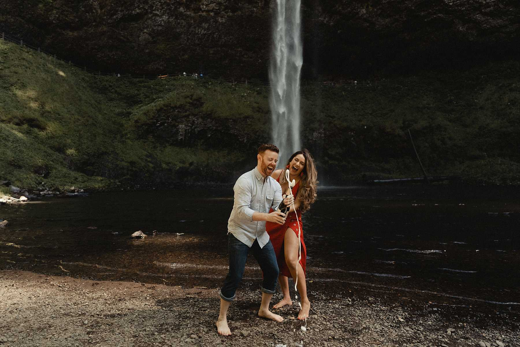Couple pops champagne during their silver falls state park engagement